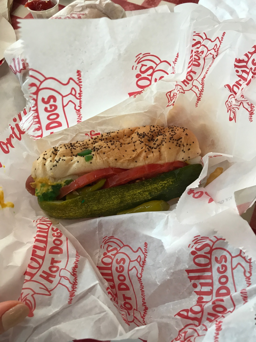 Portillo's hot dog with pickle and tomato on a poppy seed bun